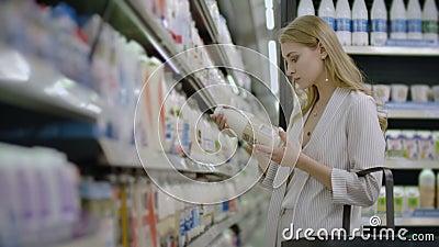 Publicidad, Negocios, Comida, Concepto de Salud - Mujer en un supermercado parada frente al congelador y elegir comprar almacen de metraje de vídeo