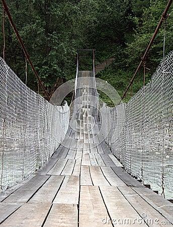 Puente colgante a través del río de la montaña