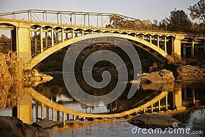 Puente del arco iris en el lago Natoma en la puesta del sol