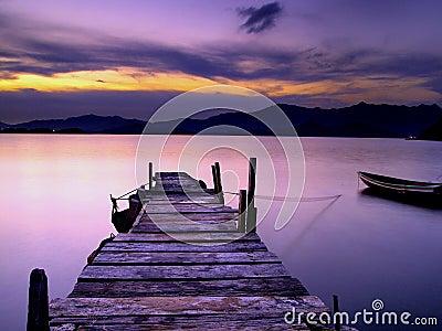 Puente y bote pequeño de madera del pie en la puesta del sol