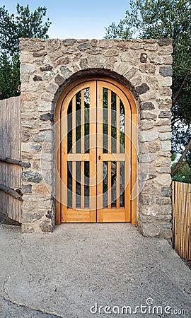 Puerta de madera en el arco de piedra vista delantera for Arcos de madera para puertas
