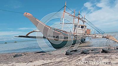 Puerto Princessa, Filippinerna Februari 30, 2019: Traditionell philippines tr?fishboat aground p? sandig kust p? stock video