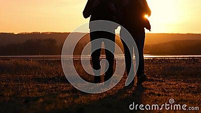 Puesta del sol de dos amigos a ir adelante, el concepto de viaje de la aventura, una mochila en los hombros almacen de metraje de vídeo