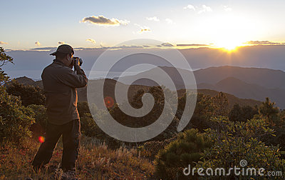 Puesta del sol de la montaña del Shooting del fotógrafo