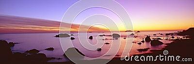 Puesta del sol en línea de la playa pacífica rocosa