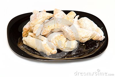 Puffed pastry covered with icing sugar on black pl