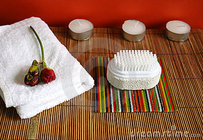 Pumice brush, candles and towel at a spa - health and beauty