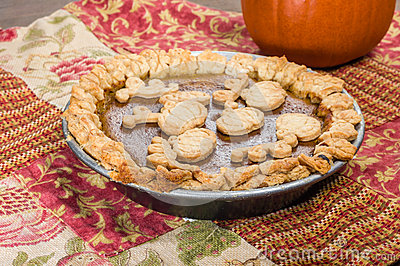 Pumkin pie with decorated crust and a pumpkin