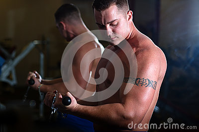 Pumped guy pulling weight in gym