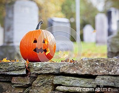 Pumpkin in graveyard with leaves