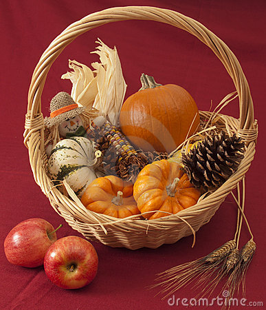Pumpkins, corn, and scarecrow doll in basket