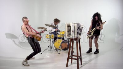 Punk rock band. Shooting a clip. Musicians are jumping with instruments. The bass player is dressed in a women`s dress. And wig. In the frame, a balalaika and a stock video footage