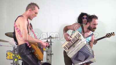 Punk rock band. Shooting a clip. Musicians are jumping with instruments. The bass player is dressed in a women`s dress. And wig. In the frame, a balalaika and a stock footage