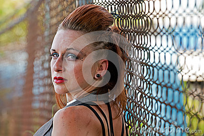 Punk woman along chain link