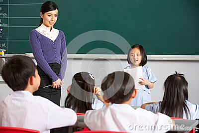 Pupil And Teacher By Blackboard In Chinese Class