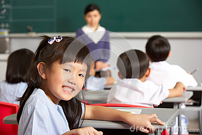 Pupil Working At Desk In Chinese School