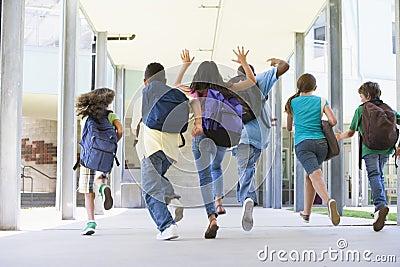 Pupilas de la escuela primaria que se ejecutan afuera