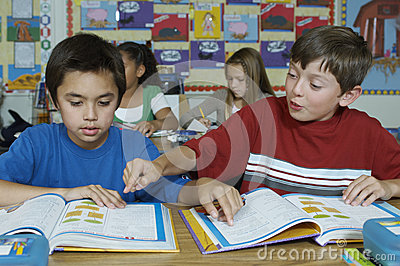 Pupils in classroom reading textbooks