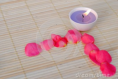 Purple candle with rose petals