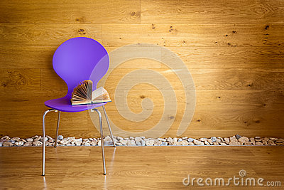 Purple chair with opened book next wooden wall