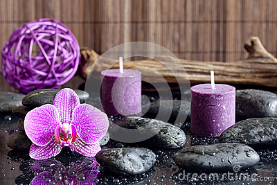 Purple orchid candles and zen stones spa concept