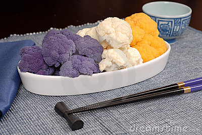 Purple, white and orange cauliflower in white serving dish