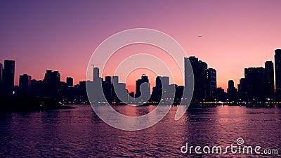 Purpurroter Sonnenuntergang an der schönen Lagune mit Skylinen See und Wolkenkratzer am Horizont Abendszene von Großstadt stock video