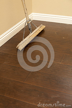 Free Push Broom On A Newly Installed Laminate Floor And Baseboard Stock Image - 25383721