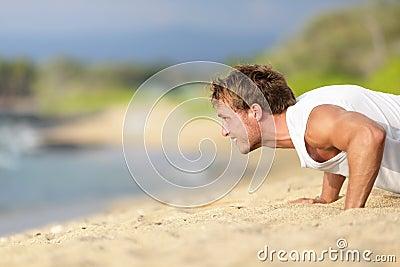 push-ups - man fitness model training on beach