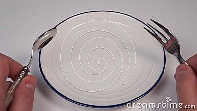 Pusty biały talerz z niebieskim obramowaniem na stole w restauracji W rękach widelca i łyżeczki deserowego zbiory wideo
