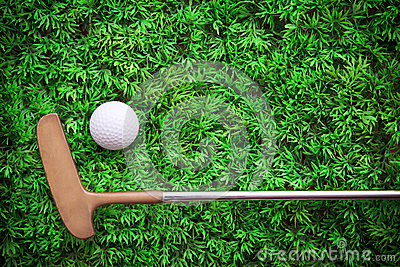 Putter and Golf ball on green grass