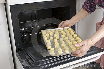 Putting dough with cheese in oven (Recipe series)