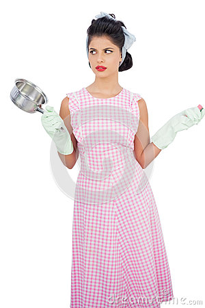 Puzzled black hair model holding a pan and wearing rubber gloves