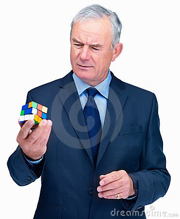 Puzzles - Senior business man holding a  cube Editorial Stock Photo