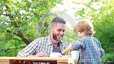 Pys och stilig fader som har frukosten i trädgården f?r?ldraskap Mat och drink f?r familj Lycklig fader med arkivfilmer