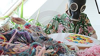 Quédate en casa, concepto divertido de cuarentenas: bordado, artesanía con máscara de gas almacen de metraje de vídeo