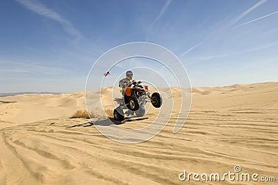 Quad Bike Rider Doing Wheelie In Desert