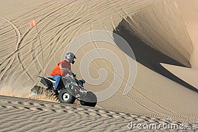 Quad rider in sand dunes bowl