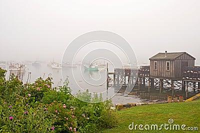 Quaint fishing wharf in fog