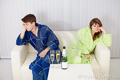 Quarrelled husband and wife at house on sofa