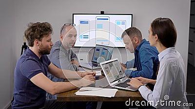 Quatro pessoas estão sentadas em uma sala de reuniões no escritório, empresa de desenvolvimento de aplicativos para celulares video estoque