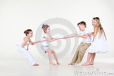 Quatro rapaz pequeno e meninas na roupa branca desenham sobre a corda