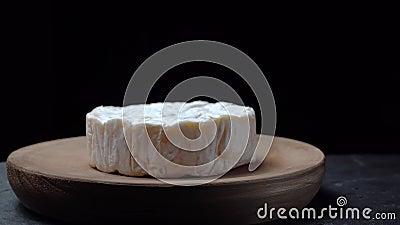 Queijo de Camembert girando sobre uma placa de madeira sobre fundo escuro vídeos de arquivo