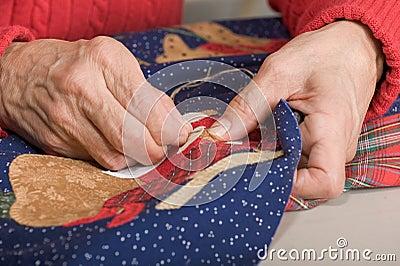 Quilter stitching quilt