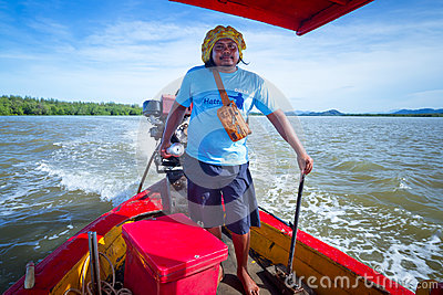 Équipez transporter des gens sur le bateau à travers la rivière Image éditorial
