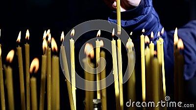 Ręka chrześcijanin zaświeca świeczkę w kościół chrześcijańskim i stawia zdjęcie wideo