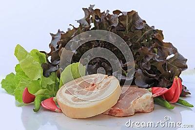 Rått griskött på skärbräda och grönsaker