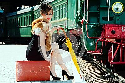 Rétro fille s asseyant sur la valise à la station de train.