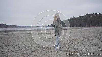 Rückansicht der jungen blond blonden Frau in Jeans und Fell am Flussufer Erwachsene Kaukasische Mädchen, die sich im Freien erhol stock video footage