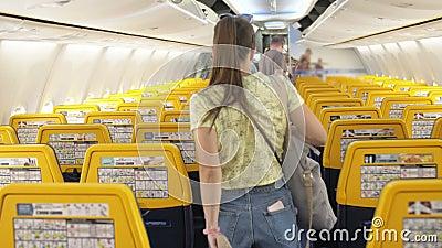 Rückansicht der jungen Frau, die mit dem Flugzeug den Gang geht stock video